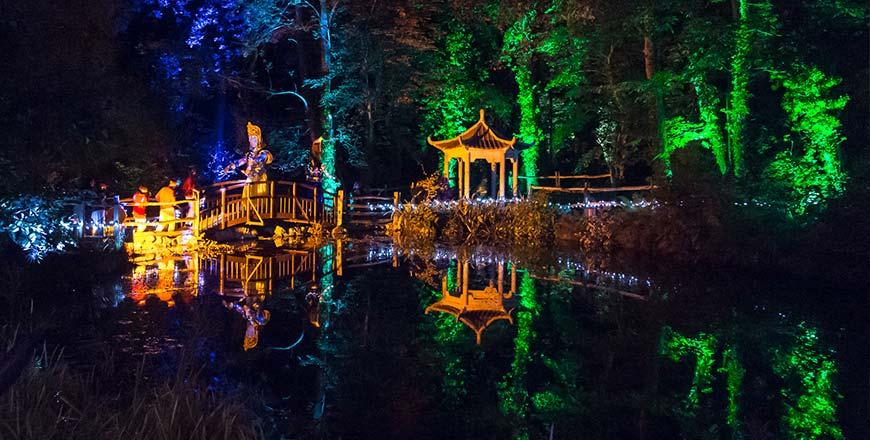 Aziatische stijl verlichte huisjes bij nacht tijdens lichtfestival Electric Woods